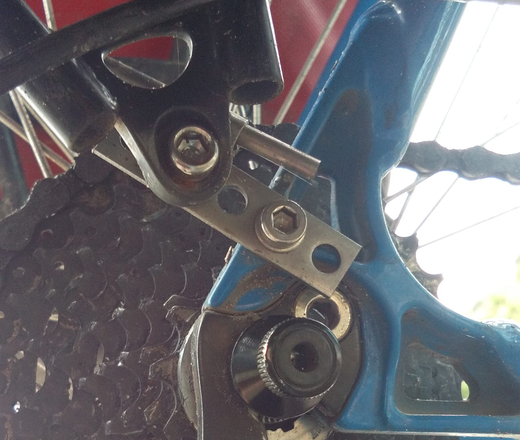 The use the disc brake mounting hole on the other side and this little piece of metal to make the other side the same length.